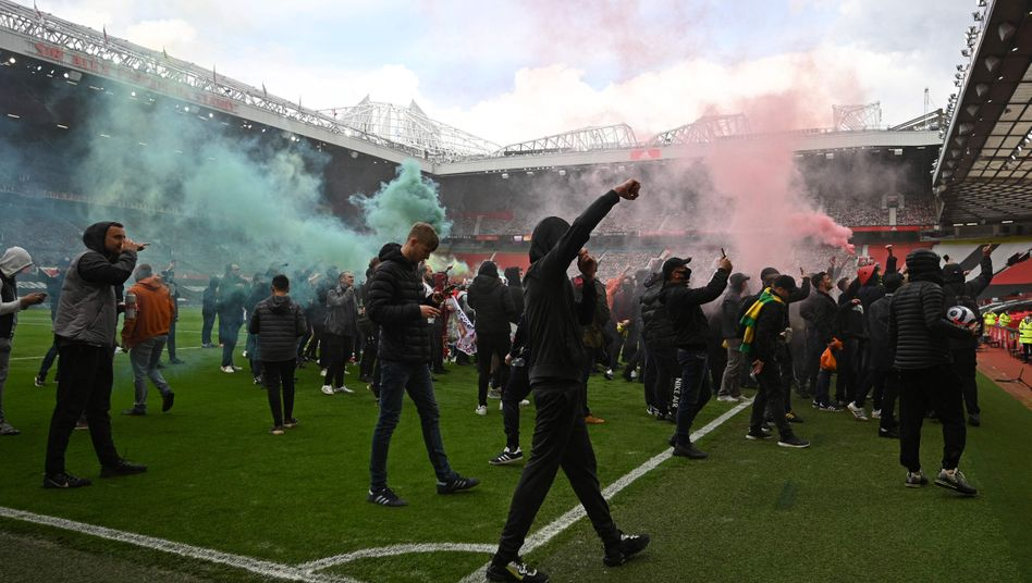Anhänger von Manchester United auf dem Rasen des Old Trafford