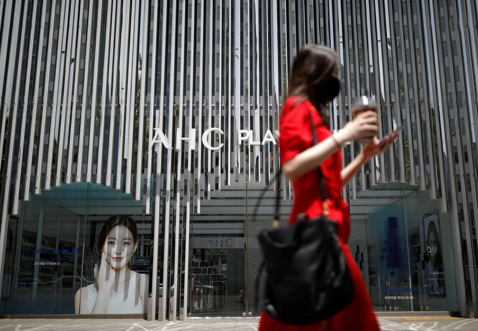 A woman holding her mobile phone walks past an AHC cosmetic store in Seoul