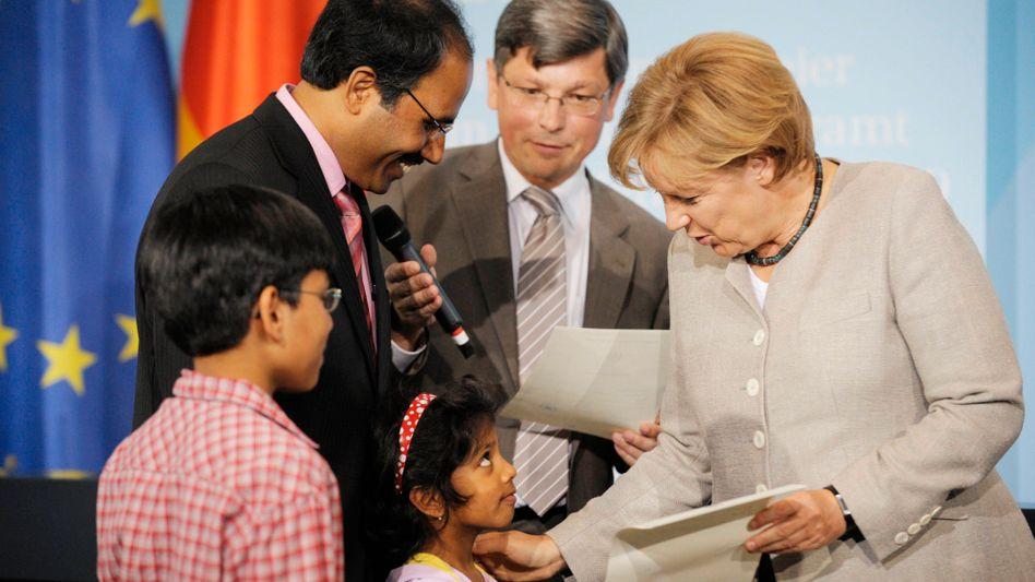 Merkel überreicht Migrantenfamilie Einbürgerungsurkunde: Künftig soll es schneller gehen