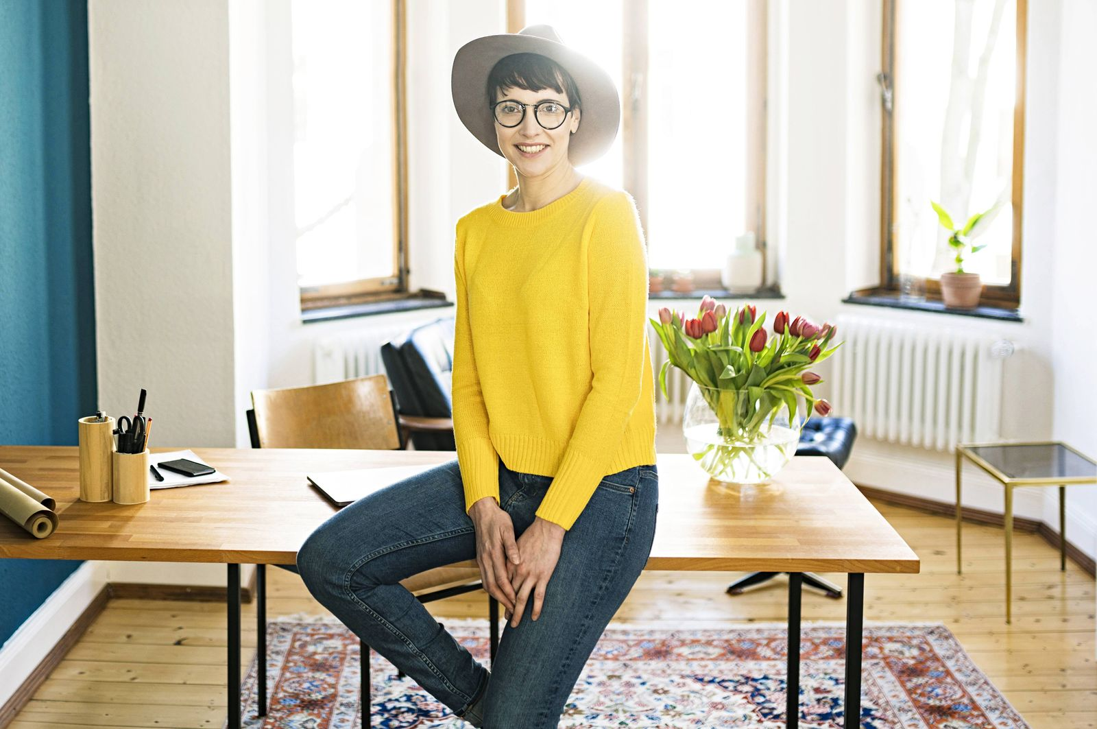 Portrait of smiling businesswoman in home office sitting on table model released Symbolfoto property