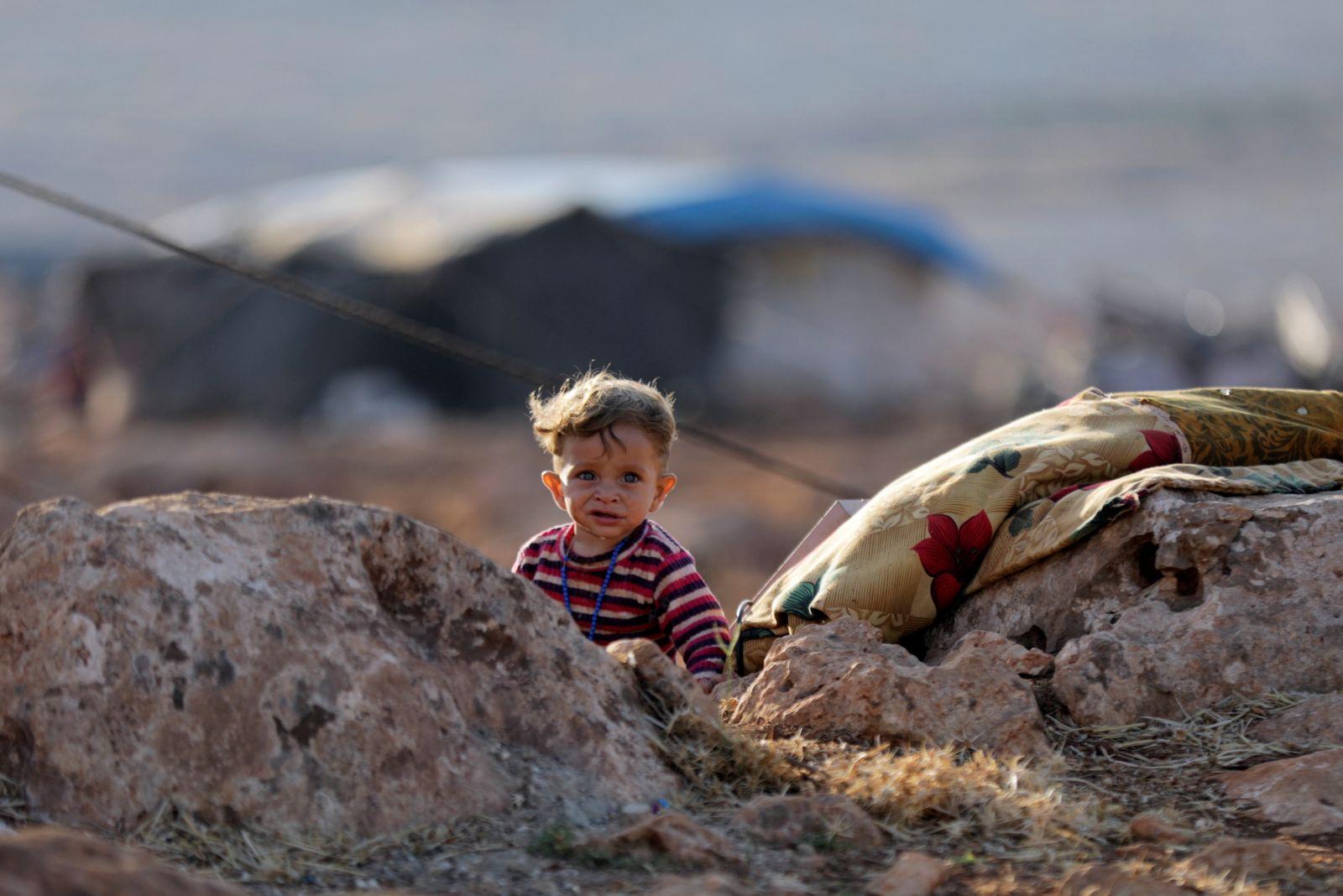 A newly displaced Syrian child walks near a refugee camp in Atimah village, Idlib province