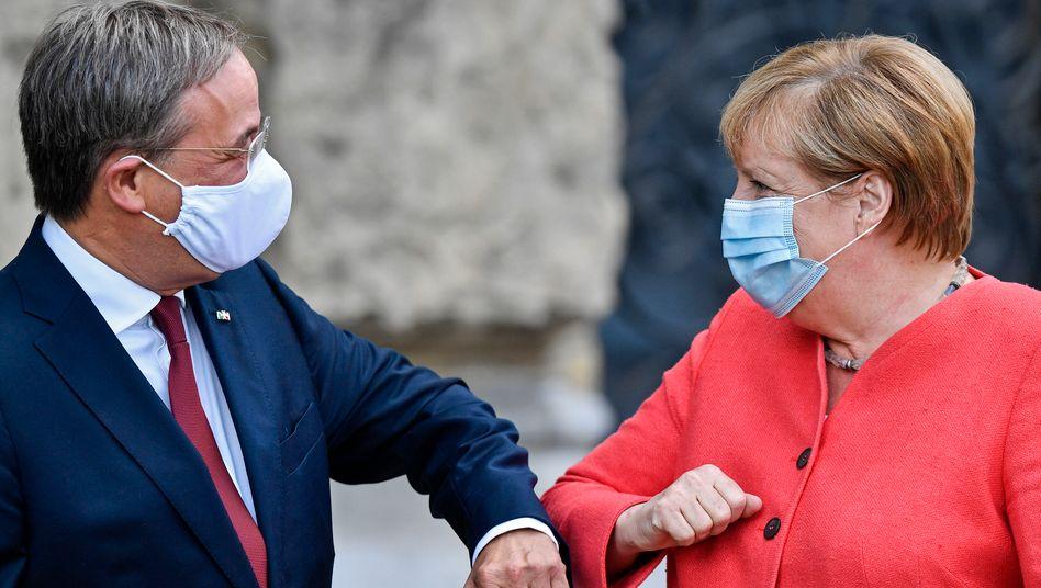 Kanzlerin Merkel mit NRW-Ministerpräsident Armin Laschet beim Ellbogencheck