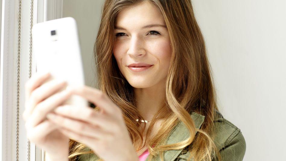 Junge Frau mit Handy: Livestreaming-Apps erobern den Smartphone-Markt