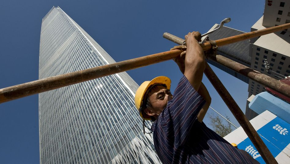 A migrant worker assembles scaffolding in front of the new China World Tower in Beijing.