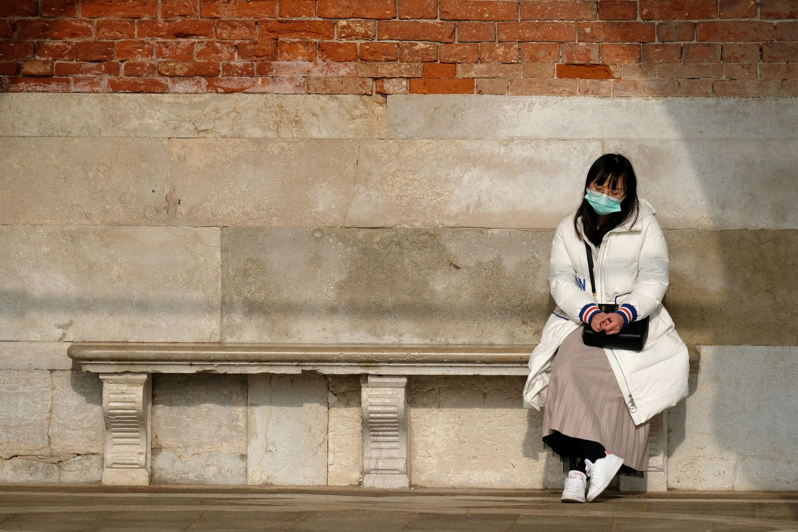 A tourist wears a protective mask in Saint Mark's Square in Venice after two coronavirus cases have been confirmed in Italy