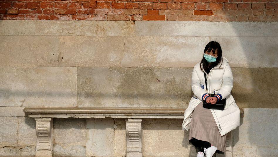 Eine Touristin trägt bei einem Venedig-Besuch eine Atemmaske, auch in Italien wurden zwei Corona-Fälle bestätigt