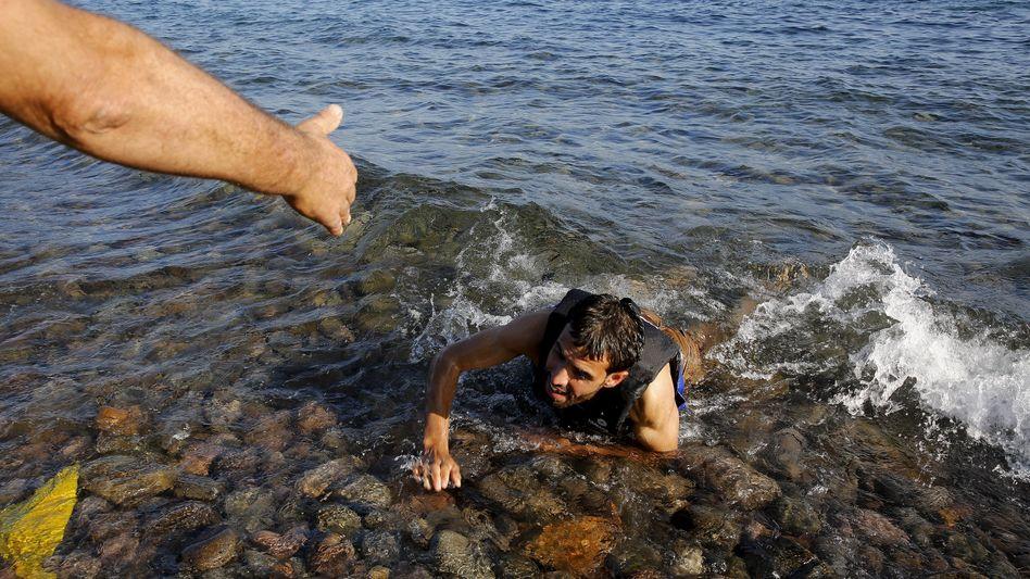 Szene auf der Insel Lesbos: Ein Mann hilft einem Flüchtling an Land