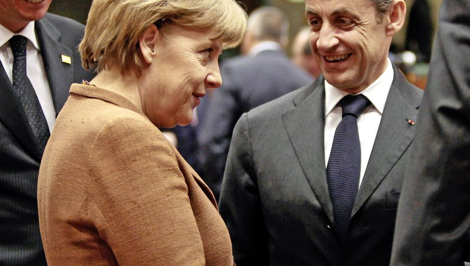 Struggling to smile: German Chancellor Angela Merkel and French President Nicolas Sarkozy at the European Union summit in Brussels.