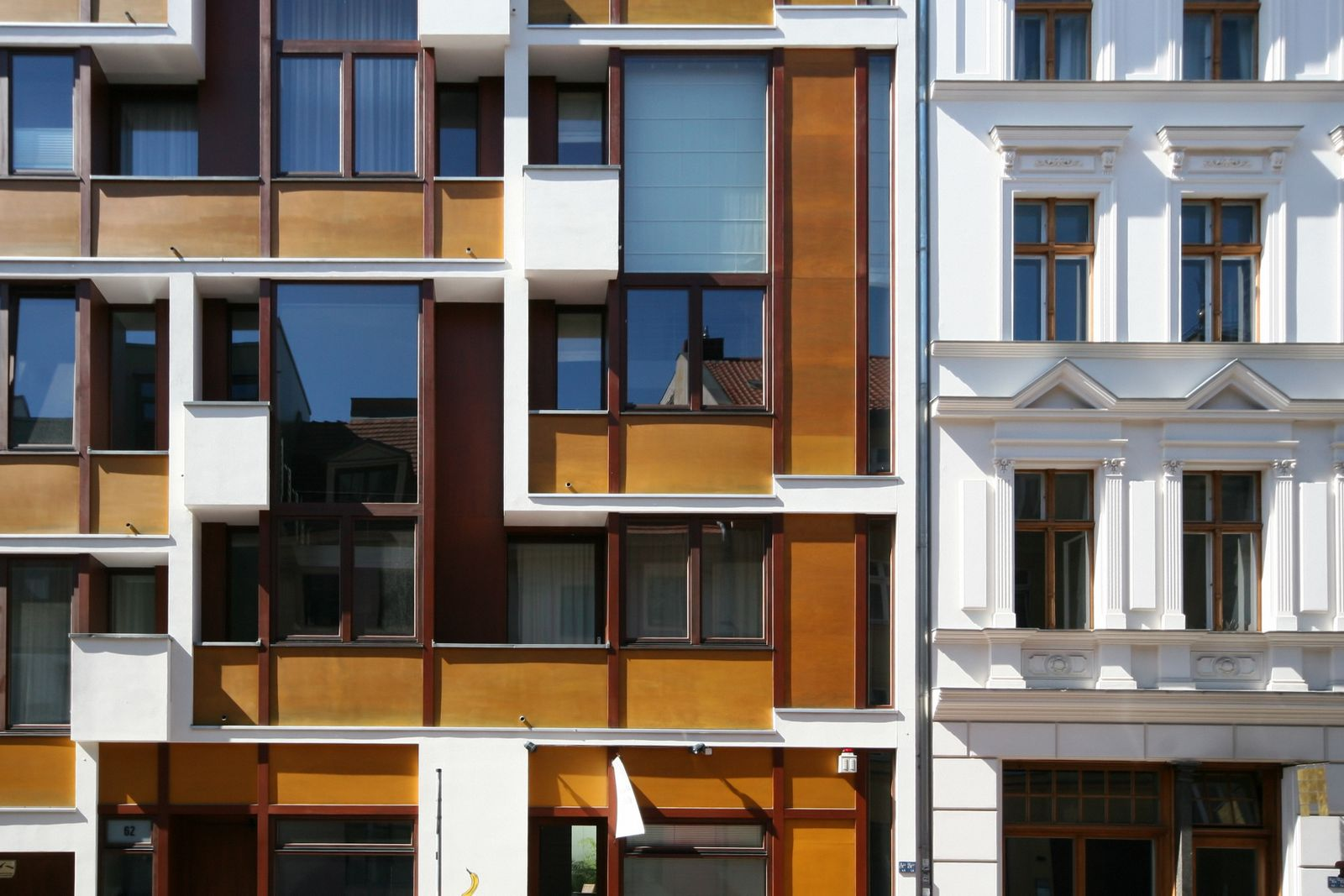 Contrast between old pre-war residential building and modern condominium housing building in the district of Mitte, in Berlin, Germany
