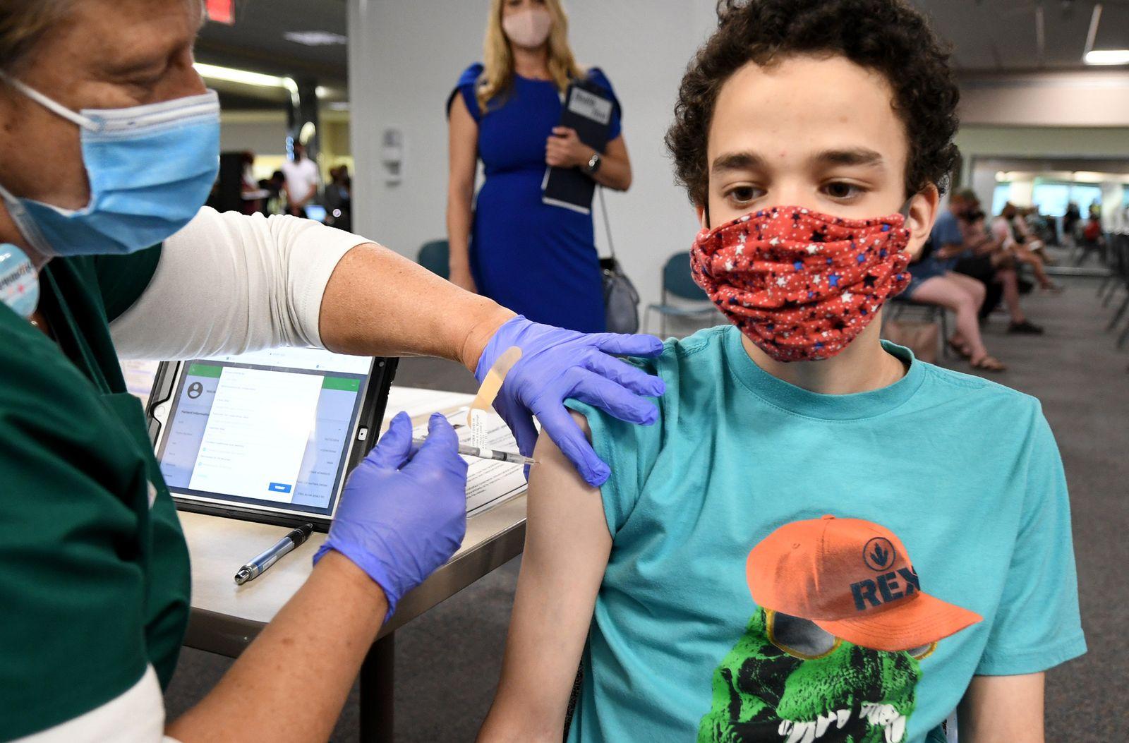 A nurse gives Malikai McPherson, 16, a shot of the vaccine