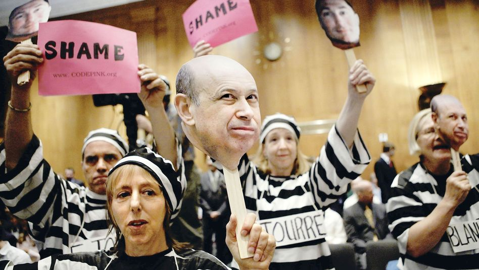Activists holding photos of Goldman Sachs CEO Lloyd Blankfein during a demonstration in Washington -- the financial market is growing as if the crisis never happened.