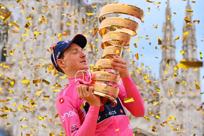 Jubel vor dem Mailänder Dom: Tao Geoghegan Hart schaut die Giro-Trophäe an