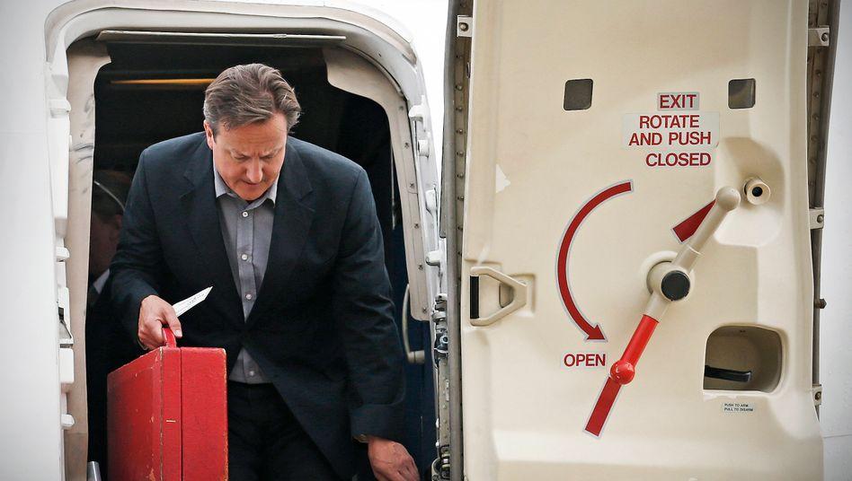 Damals noch mit rotem Koffer: Ex-Premier David Cameron beim Verlassen eines Flugzeugs (Archivbild)