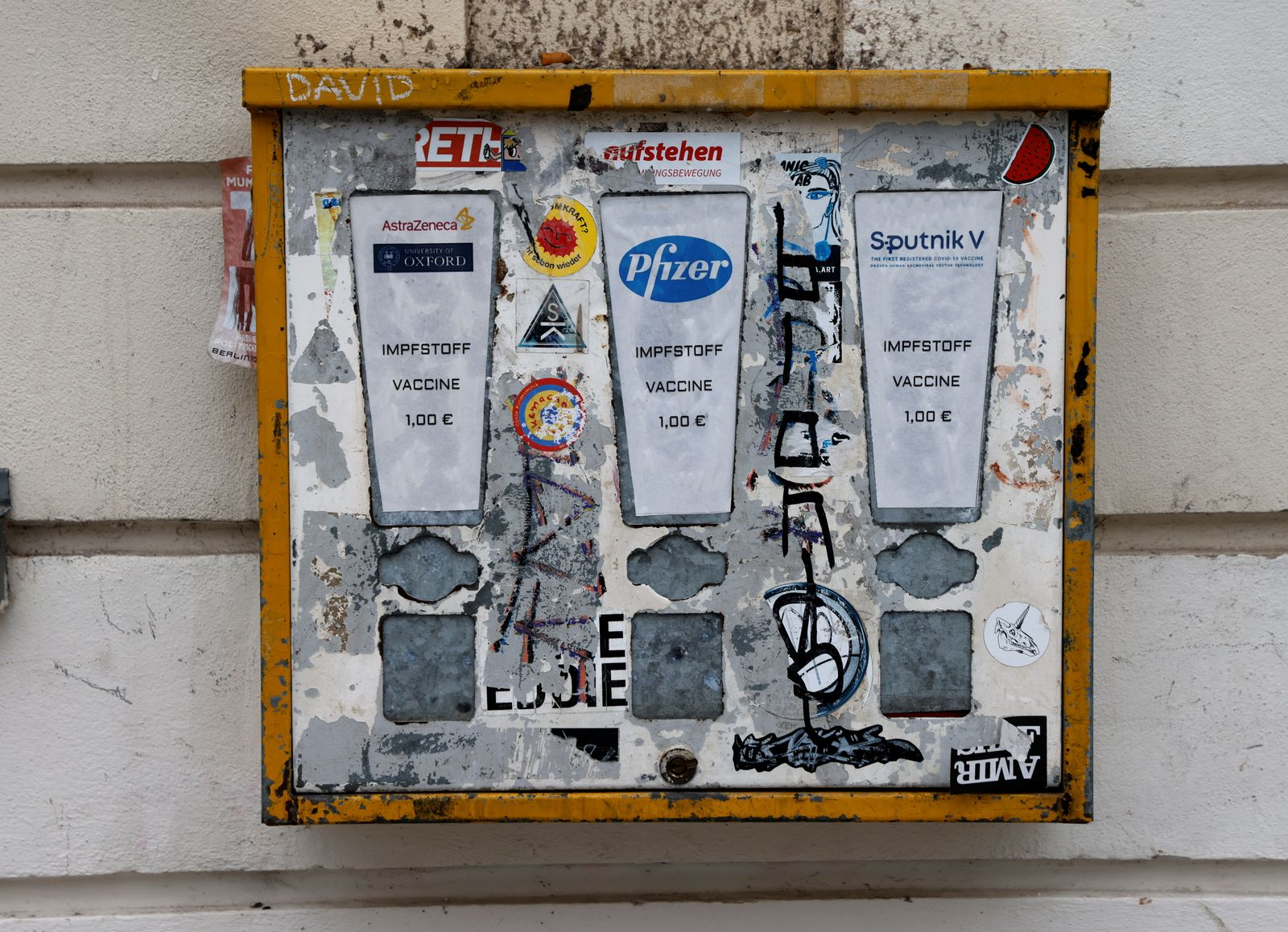 A former chewing gum vending machine pasted with coronavirus vaccine logos during lockdown in Berlin