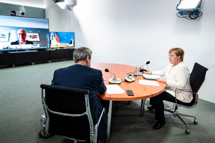 Merkel und Söder in der Schaltkonferenz, auf dem Bildschirm Hamburgs Regierungschef Peter Tschentscher