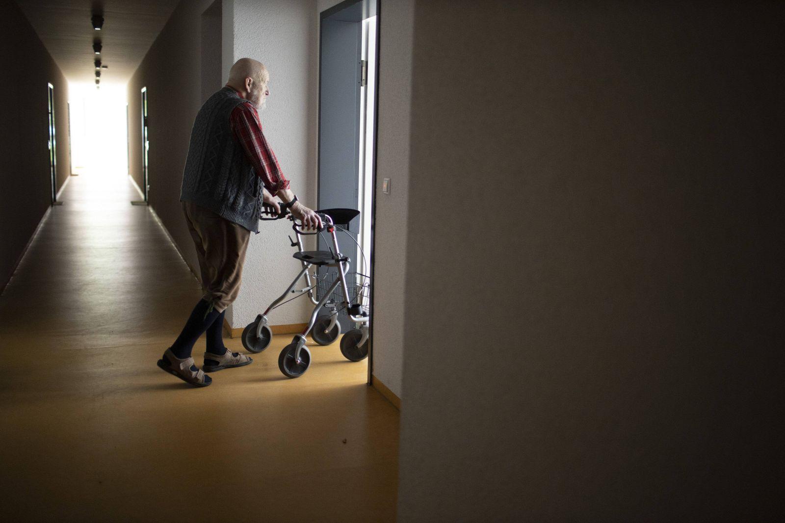 Thema: Mann mit Rollator in einem dunklen Flur. Heidelberg Deutschland *** Theme Man with walker in a dark hallway Heide