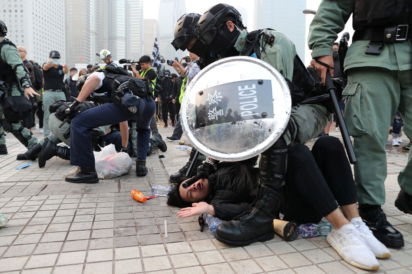Police arrest a Hong Kong protester after a Chinese flag was removed from a flag pole at a rally in support of Xinjiang Uighurs' human rights in Hong Kong