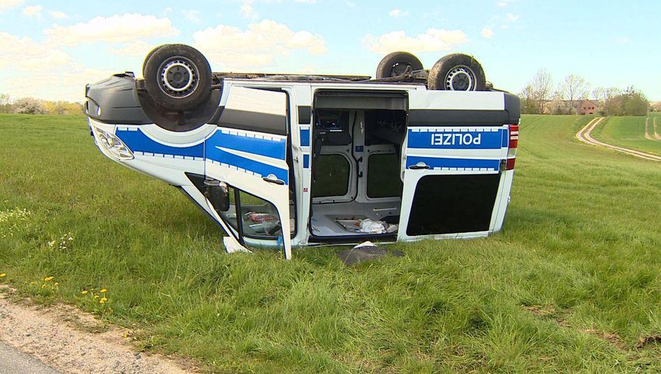 Ein Polizeiwagen liegt kopfüber auf einem Feld