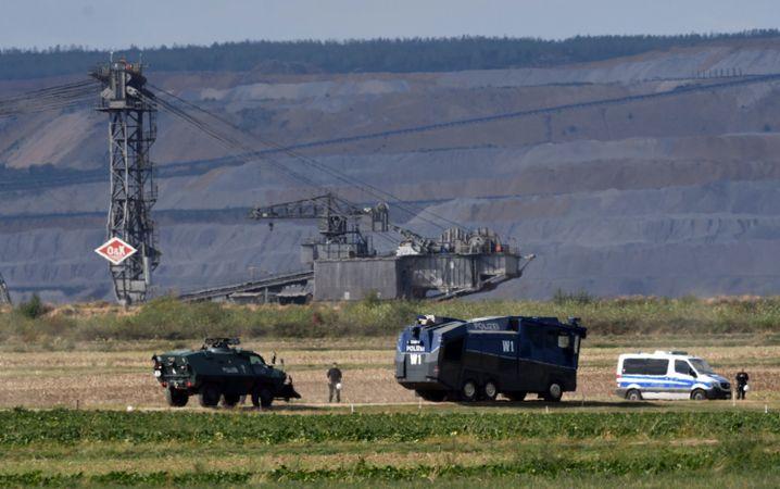 Ein Räumpanzer und ein Wasserwerfer der Polizei stehen am 15.09.18 einsatzbereit am Rand des Tagebaus Hambach