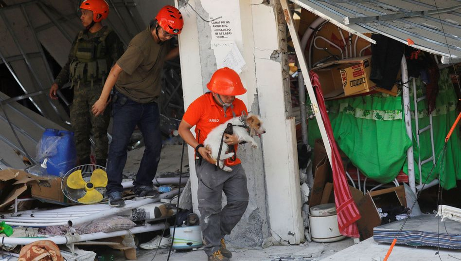 Rettungskräfte mit Suchhund in eingestürztem Gebäude in Porac