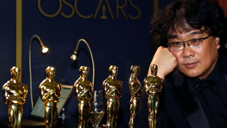 """Regisseur Bong Joon-ho posiert mit den Oscars für seinen Film """"Parasite"""""""