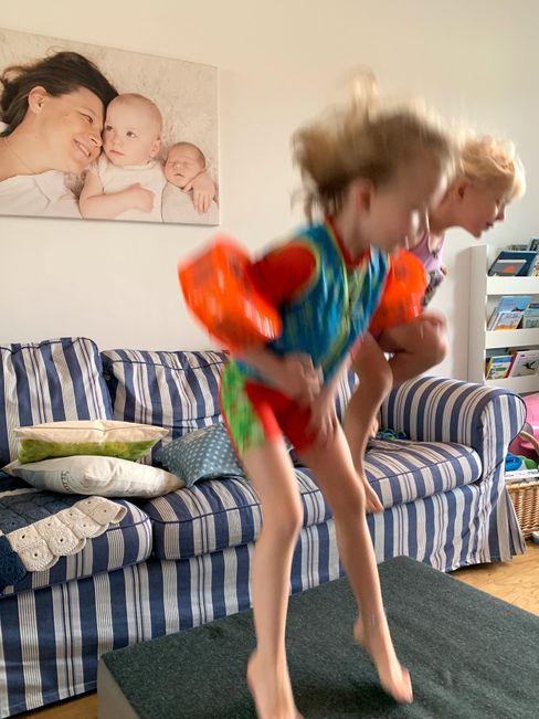 Die Mädchen spielen zu Hause, im Hintergrund ein Porträt der Familie