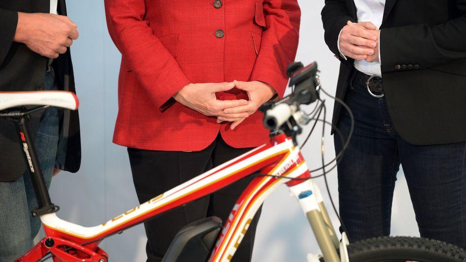 Angela Merkel, ein Fahrrad: Die CDU ist beliebt wie lange nicht, während die Städte Platz für Radverkehr machen