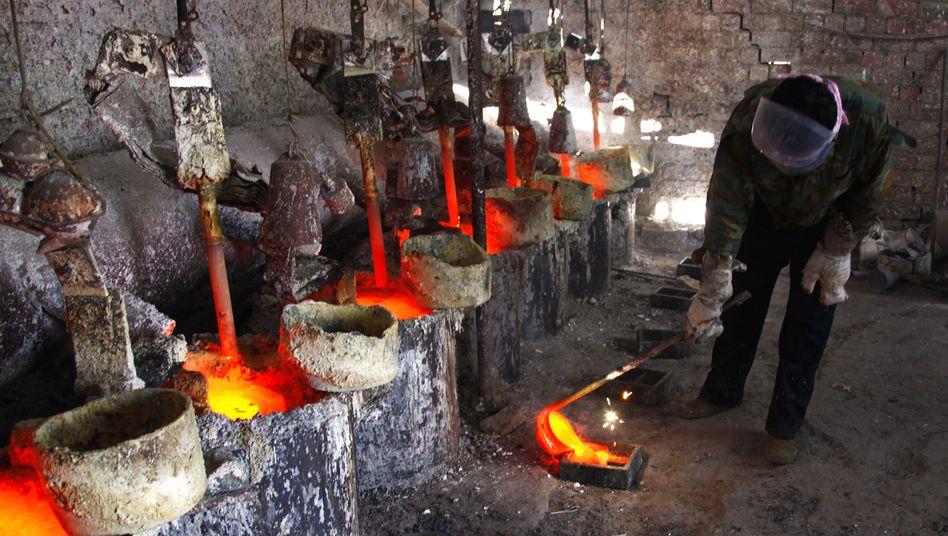 Chinesischer Arbeiter beim Gießen des Metalls Lanthan: Streit um Seltene Erden