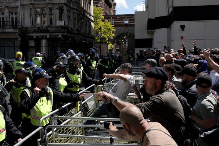 Rechtsextreme Demonstranten stoßen mit der Polizei an einer Barriere auf der Parliament Street zusammen