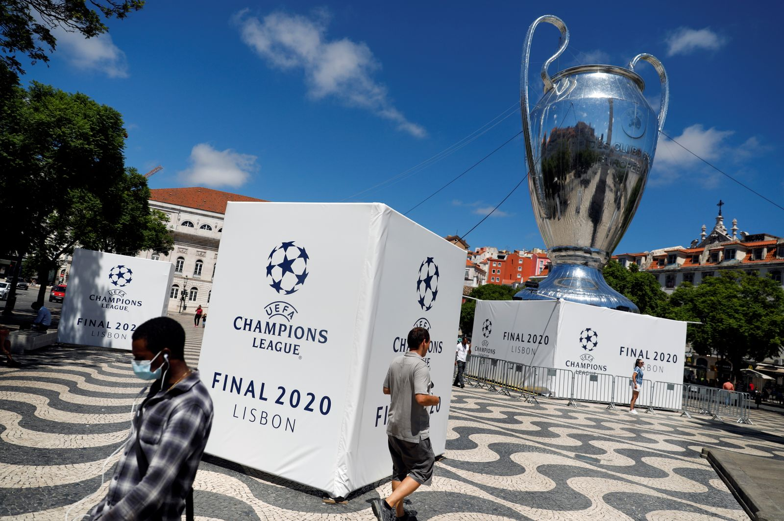 People walk near a UEFA Champions League cup recreation at the Rossio square in Lisbon