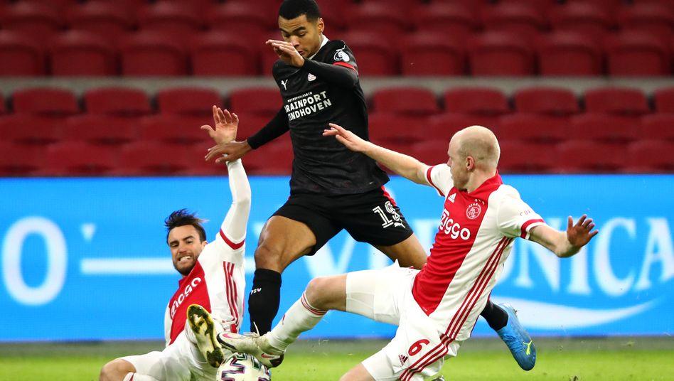 Cody Gako (M.) wird von Ajax-Spielern Nicolas Tagliafico (l.) und Davy Klaassen (r.) gestoppt