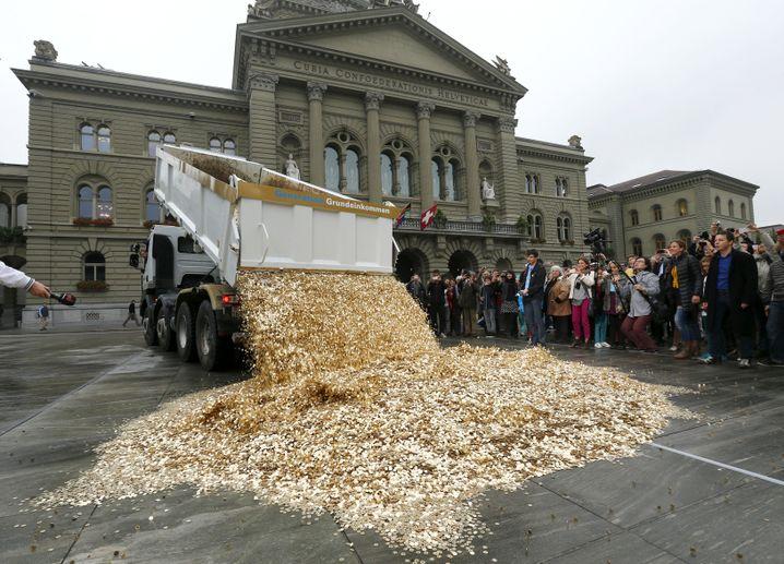 Anhänger eines Grundeinkommens kippen Münzen auf dem Bundesplatz in Bern aus (Archivbild): Alternative Verteilung des Reichtums