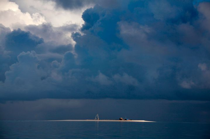 Storm clouds gathering above Bikeman Islet, located just off South Tarawa in the Pacific island nation of Kiribati. The country is facing potential evacuation as sea levels continue to rise.