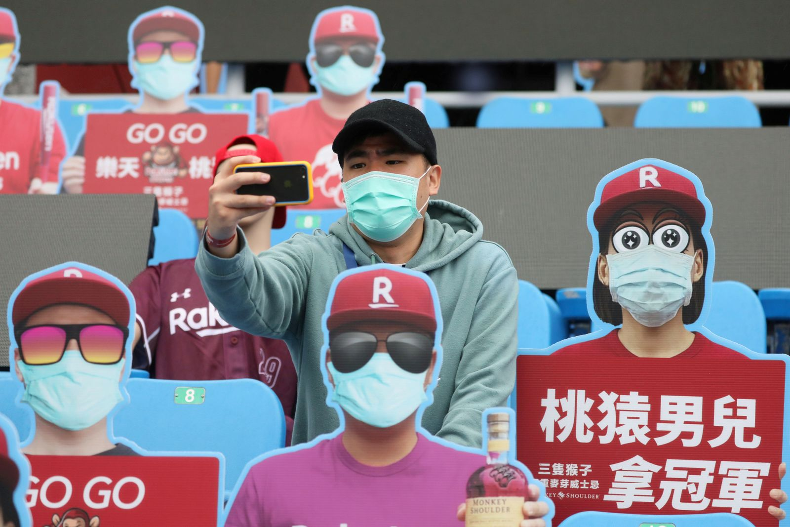 A man takes a selfie with the dummies that are used as replacements of the audience due to the outbreak of the coronavirus disease (COVID-19) at the first professional baseball league game of the season at Taoyuan International baseball stadium