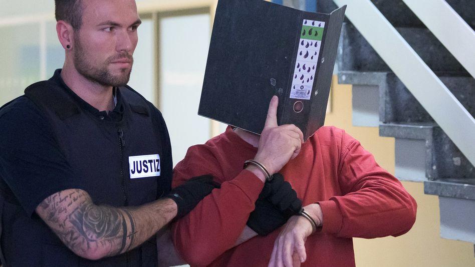Landgericht Freiburg: Der 58-jährige Angeklagte versteckt sich hinter einem mit Tränen bemalten Ordner.
