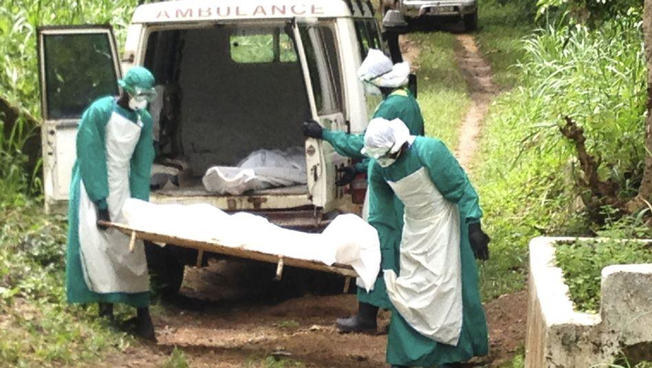 Kenema in Sierra Leone: Helfer tragen die Leiche eines Ebola-Opfers weg.