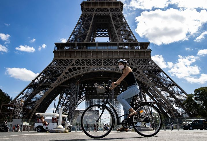 Eine Frau mit Maske radelt nahe des Eiffelturms