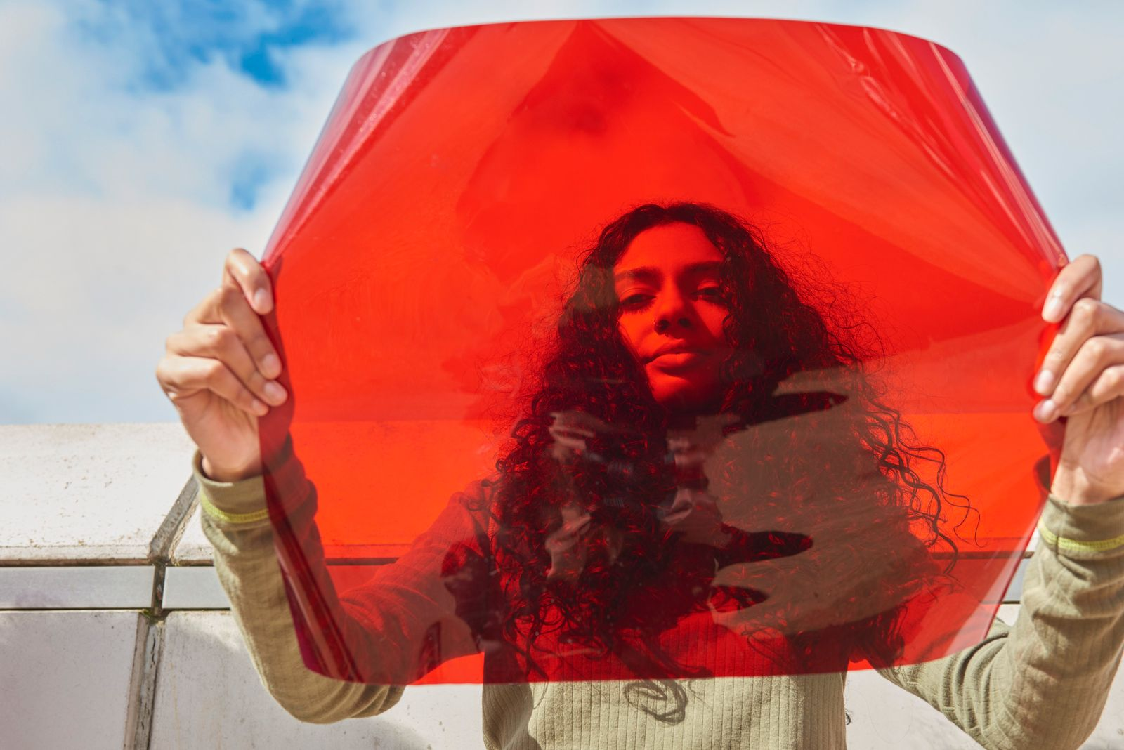 Young woman holding up red filter in front of face