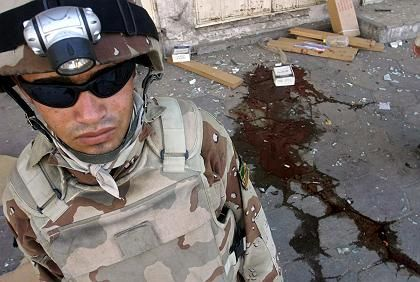 An Iraqi soldier stands guard at the site of bomb blast in central Baghdad on Friday, 02 June 2006. Two bombs hidden in plastic bags went off at the market, killing 4 civilians and injuring 32.