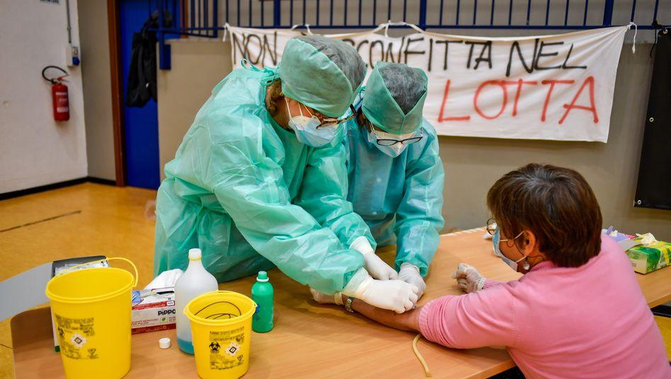 Aufnahme aus dem April: Medizinische Mitarbeiter in Schutzanzügen entnehmen eine Probe für serologische Tests zur Erfassung von Covid-19-Antikörpern in Cisliano