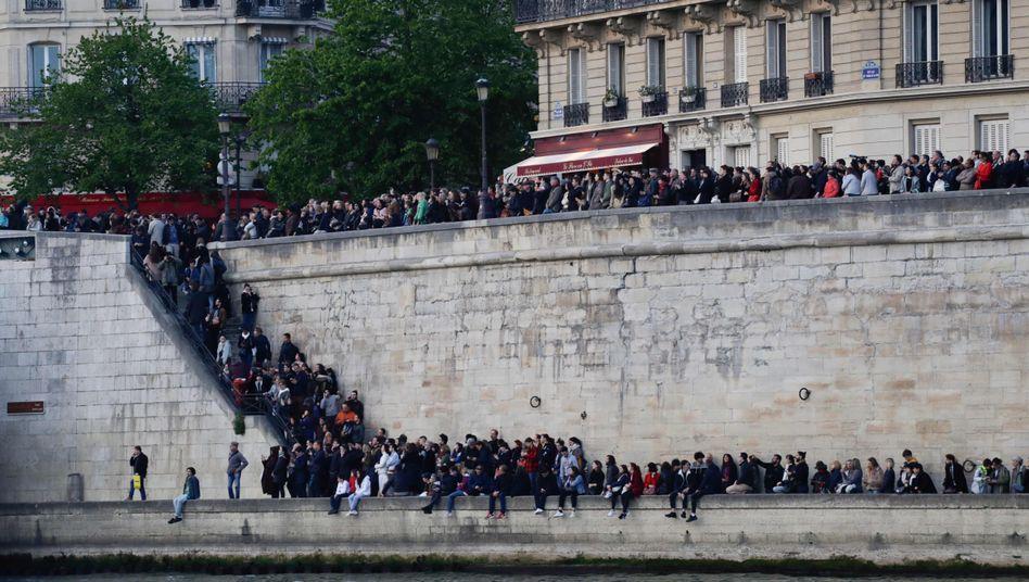 Menschen sitzen in Paris am Ufer der Seine und schauen Richtung Notre Dame