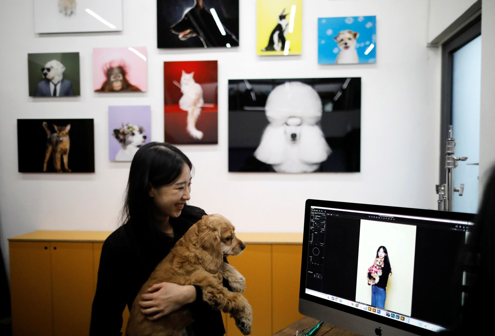 A woman looks at pictures at a pet studio in Seoul