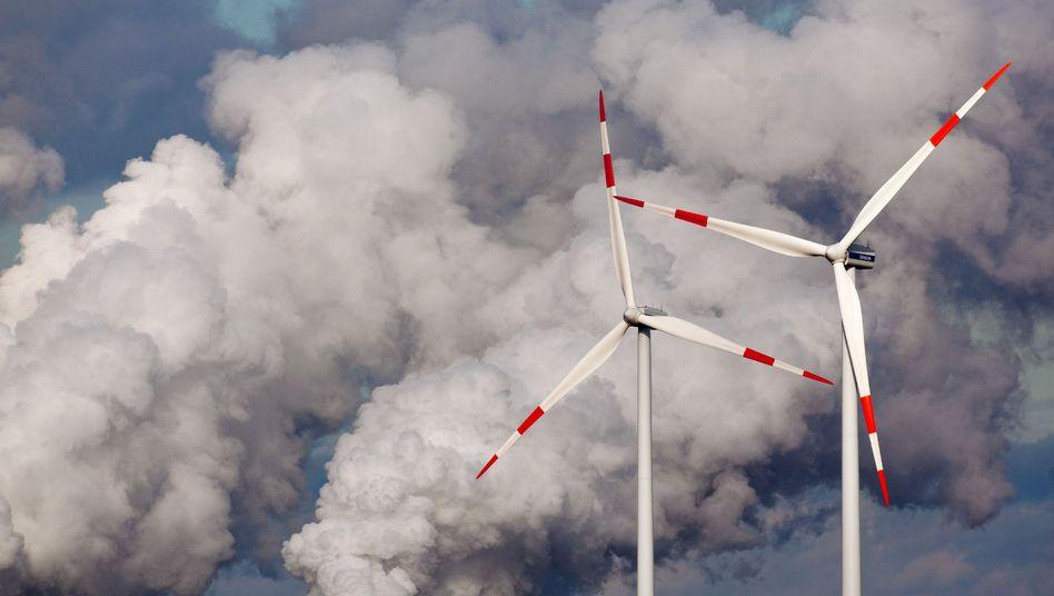 Windräder vor den Kühltürmen des Braunkohlekraftwerks im brandenburgischen Jänschwalde.
