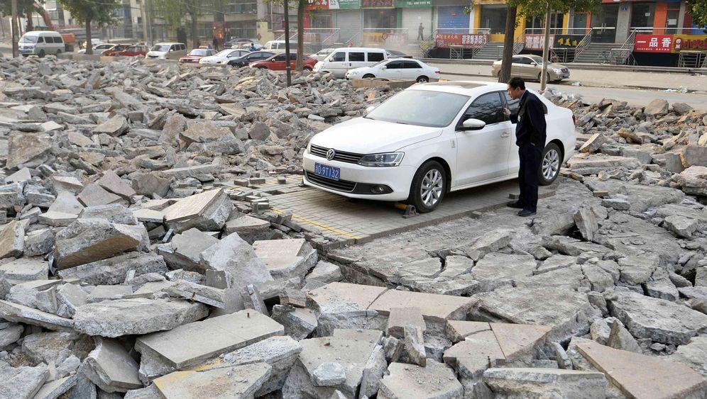 Bauen in China: Auto von Bauschutt umzingelt