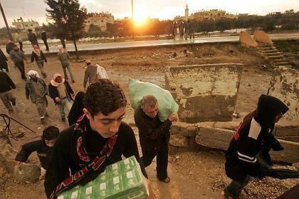 """Palästinenser tragen Waren über die offene Grenze aus Ägypten in den Gaza-Streifen: Neue Lieferungen sollen """"humanitäre Katastrophe"""" verhindern"""