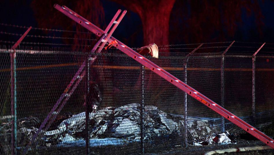 Das Wrack des abgestürzten Kleinflugzeugs liegt in der Nähe eines Zauns, der den Flugplatz Dillingham auf Hawaii umgibt.