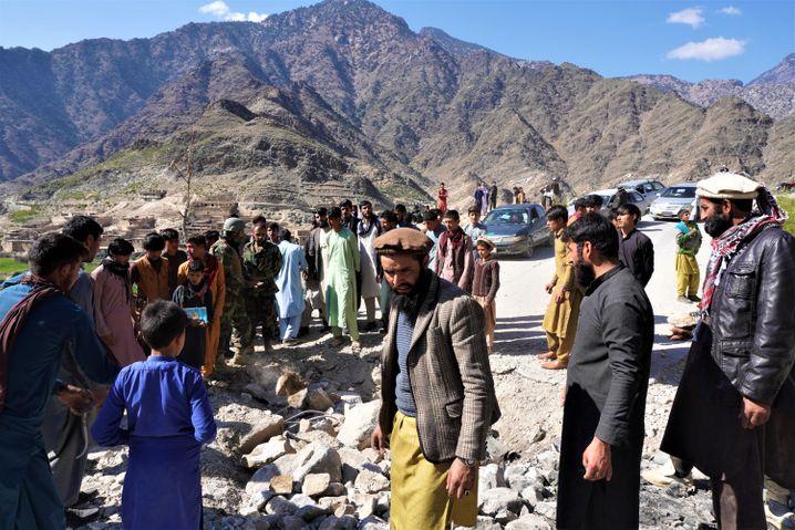 Zivilisten reparieren im Pech-Tal die bei Kämpfen beschädigte Straße