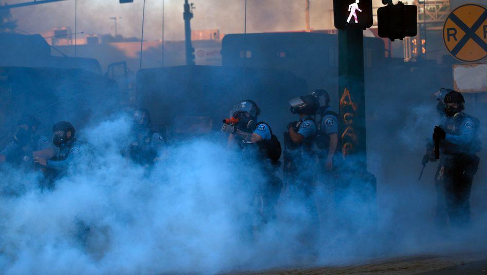 Polizisten im Rauch von Minneapolis: Laut Gouverneur Tim Waltz wurden sie von Demonstranten beschossen