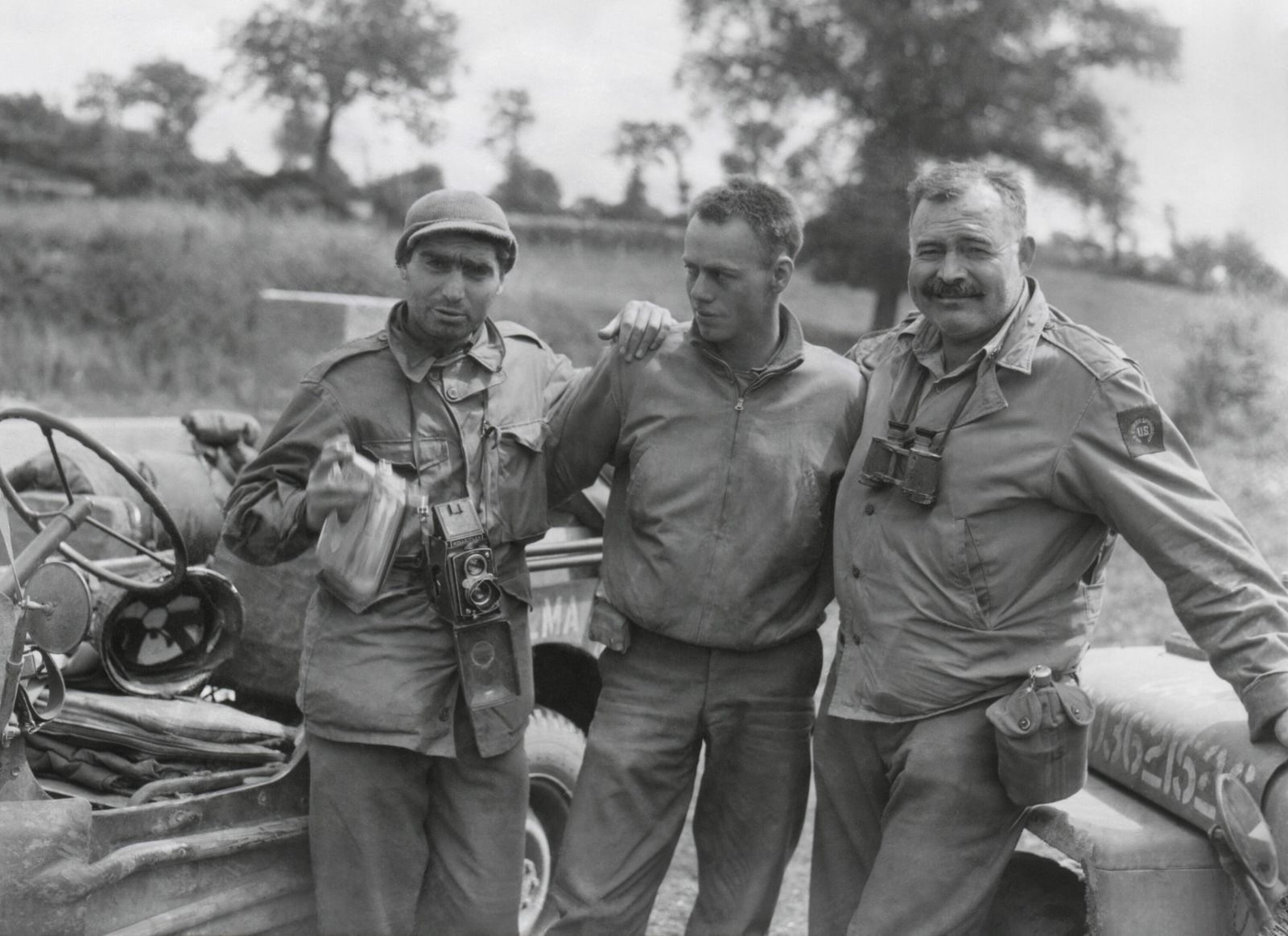 Robert Capa (left) and Ernest Hemingway (right) with their driver U.S. Army driver. They are waiting to follow an Americ