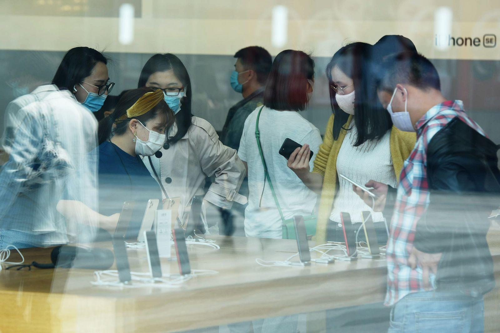 People are seen at an Apple store as the new iPhone SE goes on sale in Hangzhou
